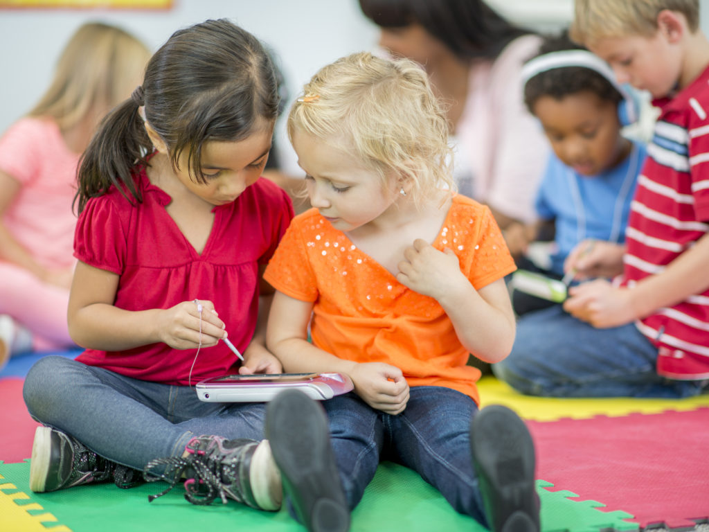 Two little girls are sitting on a mat at preschool in their multi-ethnic class, playing on an electronic reading device.